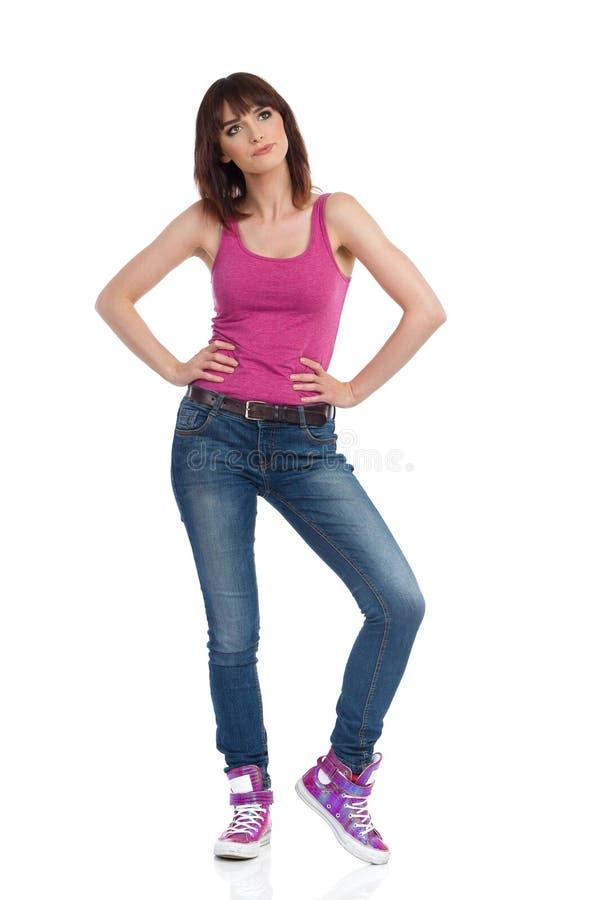 做鬼脸的年轻女人站立用在臀部的手并且看  免版税库存照片