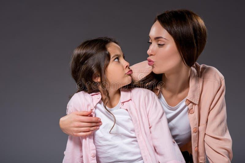 做鬼脸的母亲和女儿 库存图片
