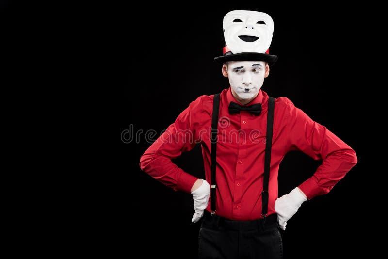 做鬼脸的笑剧用两手插腰的手和在帽子的面具 免版税图库摄影