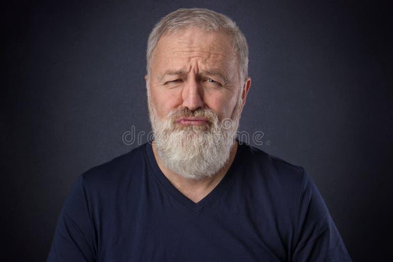 做鬼脸的老人喜欢一个被损坏的孩子 免版税库存图片