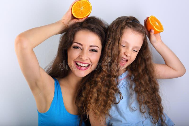 做鬼脸的joying的幽默年轻母亲和逗人喜爱的长的头发女儿 免版税库存图片