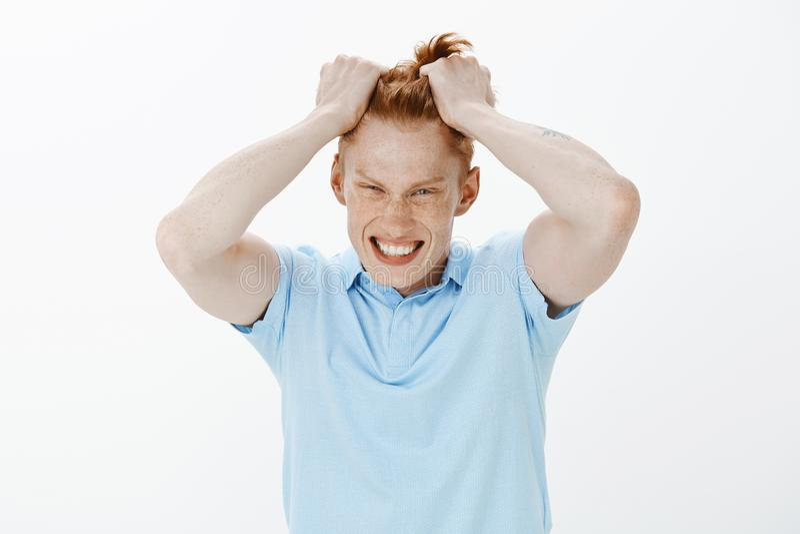 做鬼脸被迫使的沮丧的英俊的红头发人人腰部的射击有雀斑的,拔出头发和,小便 免版税库存图片
