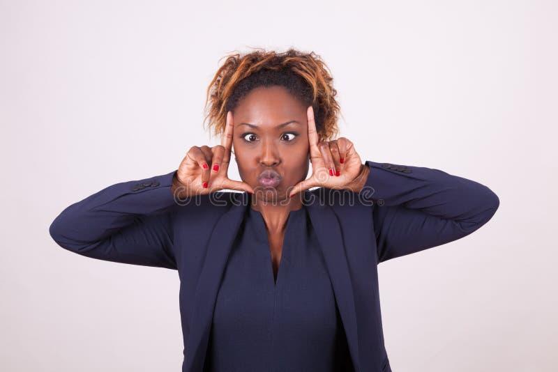 做鬼脸非裔美国人的女商人做框架姿态w 免版税库存照片