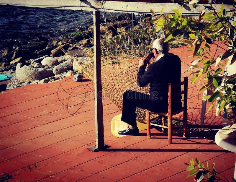 做鱼陷井的老人由芦苇在南意大利 库存照片