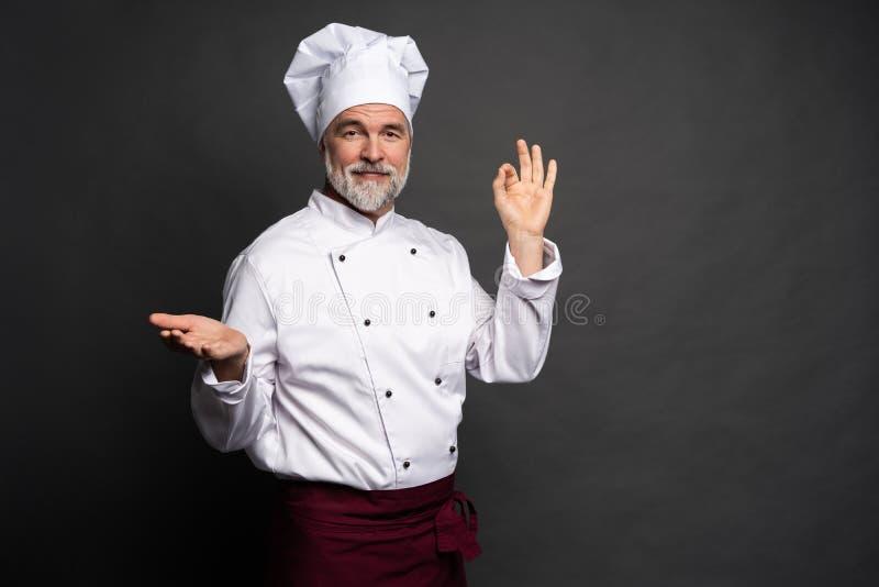 做鲜美可口姿态的厨师由亲吻的手指 白色制服的确信的有胡子的男性厨师有完善的标志的 免版税库存照片