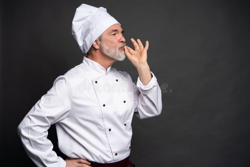 做鲜美可口姿态的厨师由亲吻的手指 白色制服的确信的有胡子的男性厨师有完善的标志的 库存照片