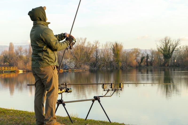 做鲤鱼钓鱼的渔夫 免版税库存图片