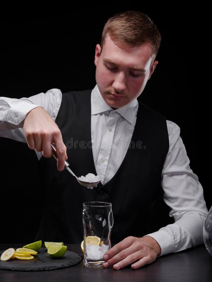 做鸡尾酒的一位英俊的侍酒者在黑背景 增加冰的男服务员到震动 刷新的酒精概念 免版税图库摄影