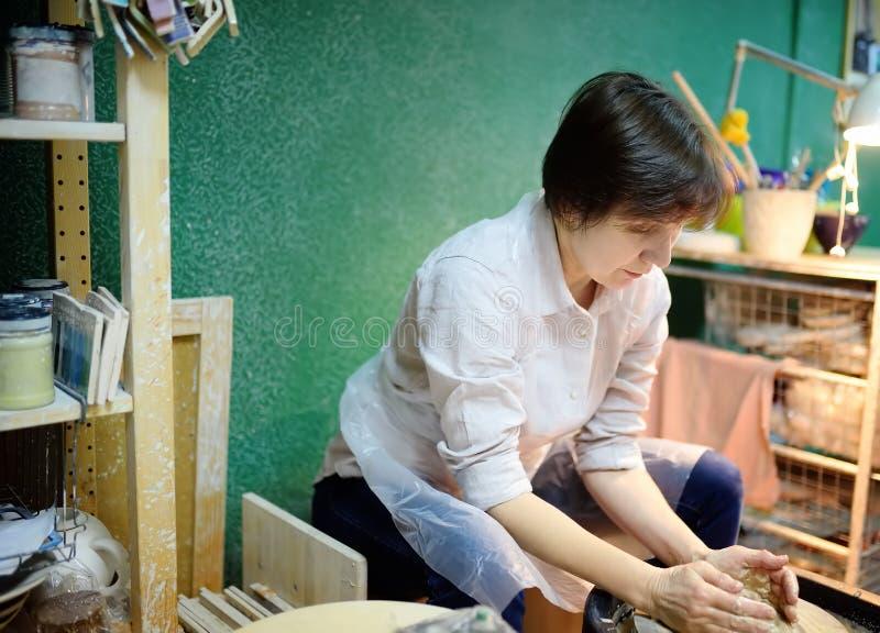 做黏土对象的中年妇女 在工作期间的雕刻家在瓦器车间 免版税图库摄影