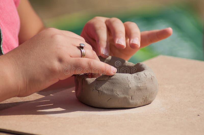 做黏土瓦器的孩子的手在室外滚保龄球 免版税库存图片