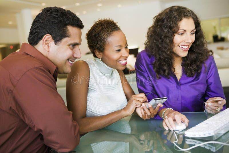 做购买的夫妇通过在家具店的计算机 免版税库存照片