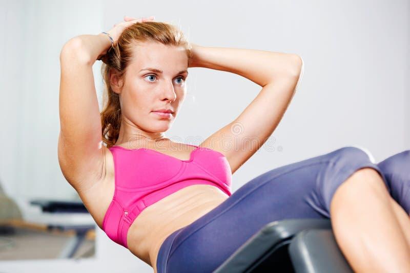 做仰卧起坐的运动妇女 库存照片