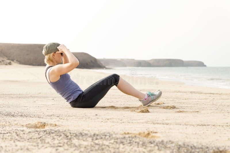 做仰卧起坐的活跃妇女由海滩 库存图片