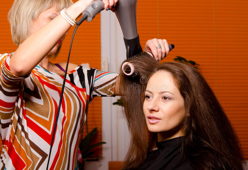 做头发的美发师美丽的愉快的女孩 免版税库存照片