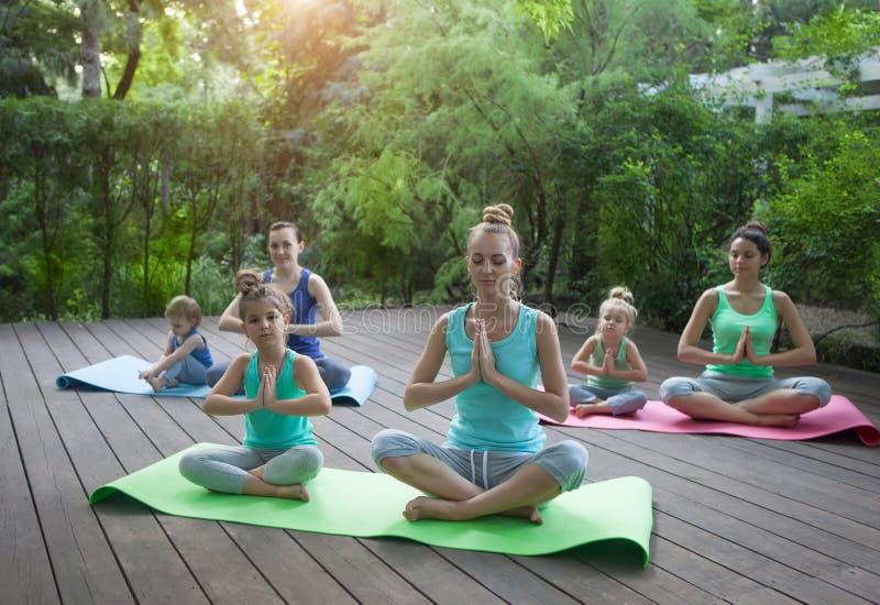 做锻炼实践的瑜伽的母亲和女儿户外 图库摄影