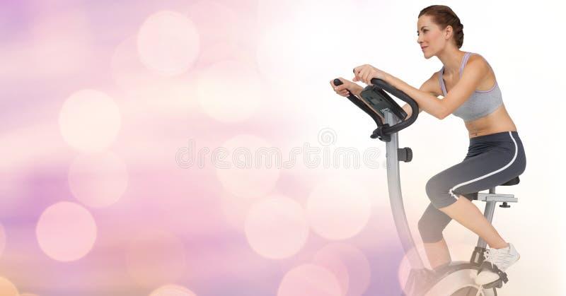 做锻炼脚踏车有桃红色背景的少妇 库存图片
