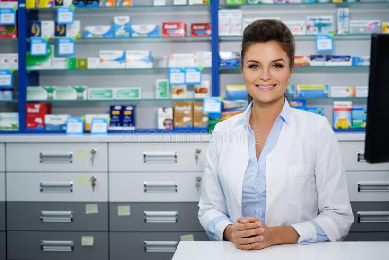 做他的美丽的微笑的少妇药剂师在药房的工作 免版税库存照片