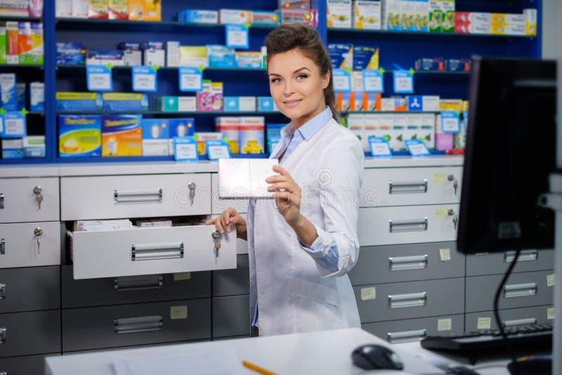 做他的美丽的微笑的少妇药剂师在药房的工作 免版税库存图片