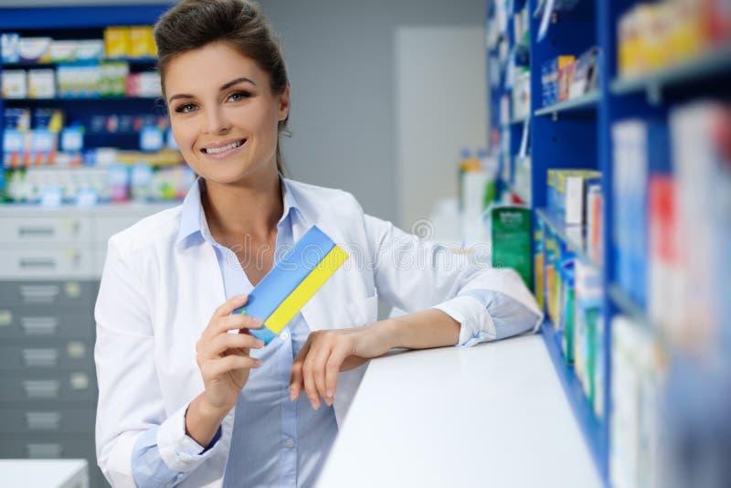 做他的美丽的微笑的少妇药剂师在药房的工作 库存照片