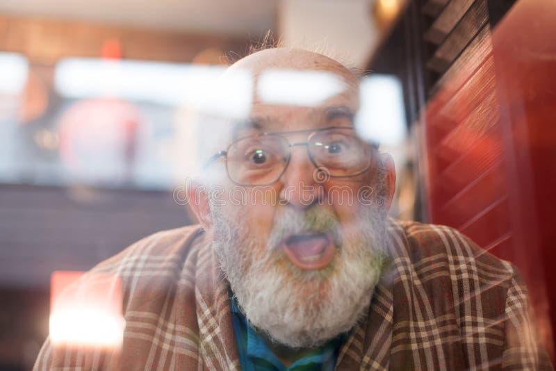 做滑稽的面孔的老人通过窗口 库存图片