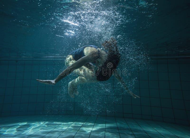做翻筋斗水中的运动游泳者 库存照片