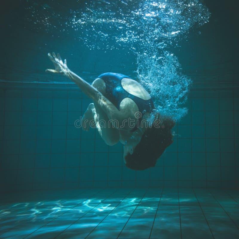 做翻筋斗水中的运动游泳者 库存图片