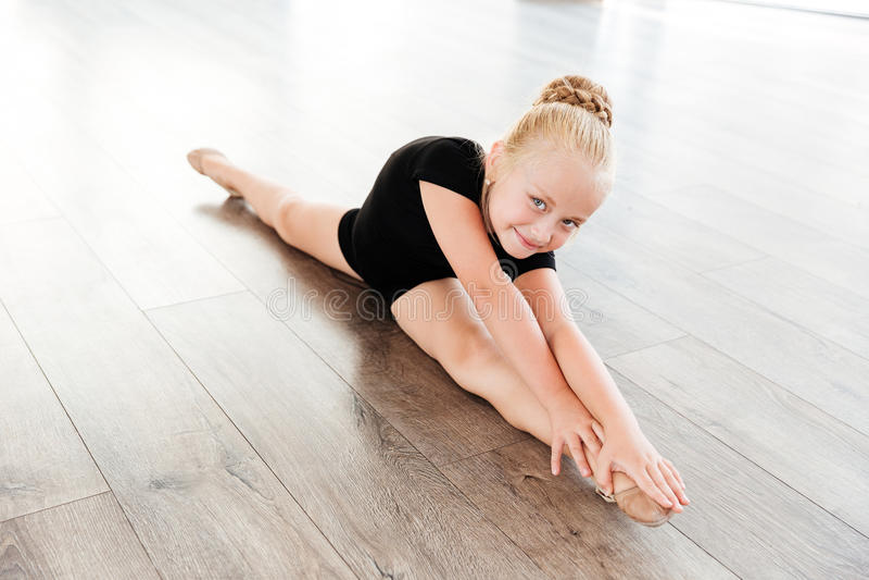 做麻线的小女孩芭蕾舞女演员在芭蕾演播室 免版税库存图片