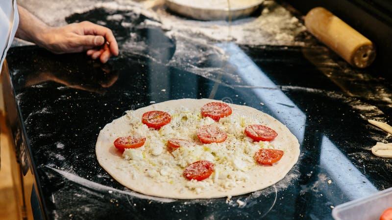 做Caprese天卫八比萨的厨师通过增加橄榄油在面团用切的蕃茄、无盐干酪和帕尔马干酪在烘烤前 免版税库存图片