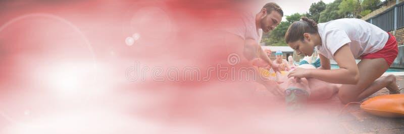 做CPR的救生员在与转折的游泳池 免版税库存照片