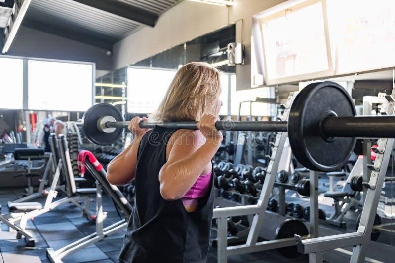 做heavylifting的锻炼的健身房的年轻适合的妇女 女性a 免版税库存照片