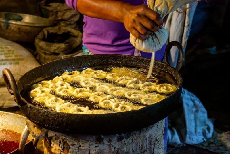 做jalebi,一顿甜快餐的人做通过油炸在椒盐脆饼或环形轧材的多用途面粉面团,然后被浸泡 免版税图库摄影