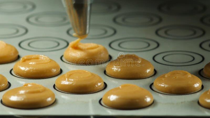 做macaron,法国点心,紧压烹调袋子的面团形式 食品工业、大量或者批量生产 免版税库存照片
