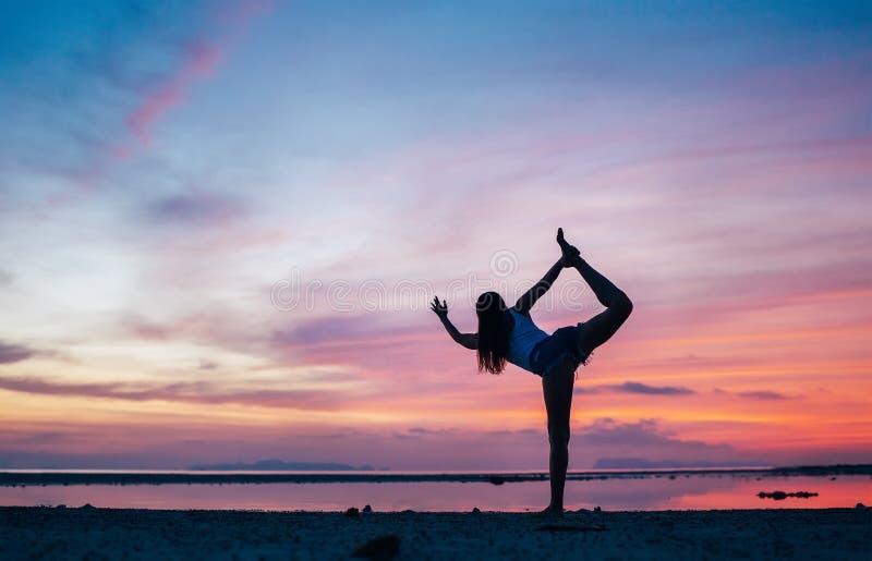 做natarajasana瑜伽姿势的少女在日落海边 活跃天起点概念图象 库存照片