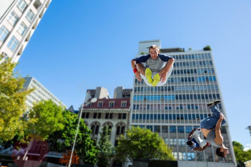 做parkour的愉快的朋友在城市 免版税图库摄影