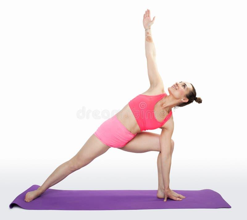 做pilates的年轻深色的妇女在被隔绝的席子行使 免版税库存图片