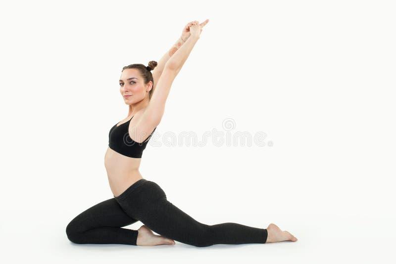 做pilates锻炼的年轻深色的妇女被隔绝 免版税图库摄影