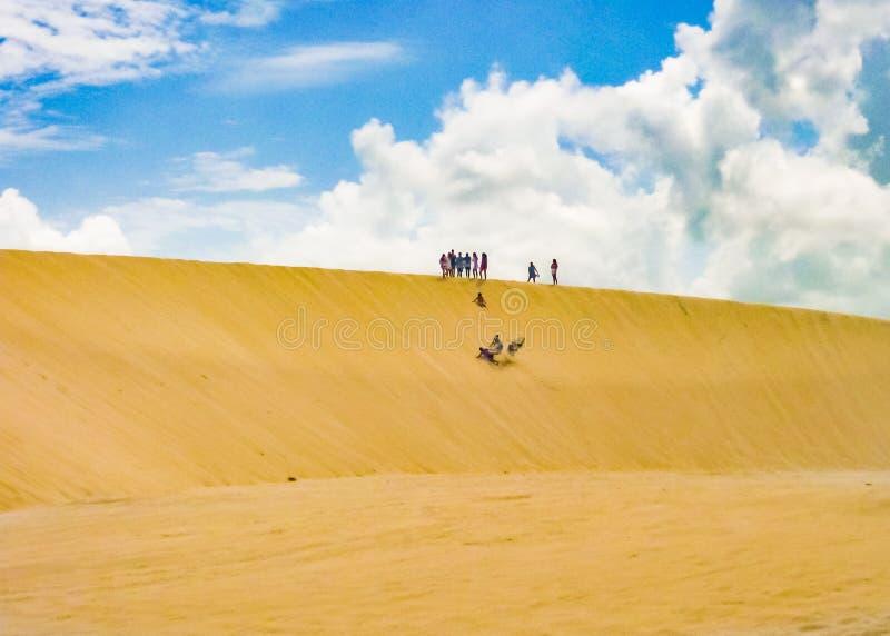 做Sandboarding的人们在沙丘Jericoacoara巴西 库存照片
