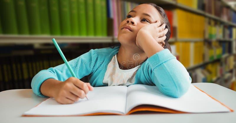 做schoolwork的女孩在教育图书馆里 库存图片