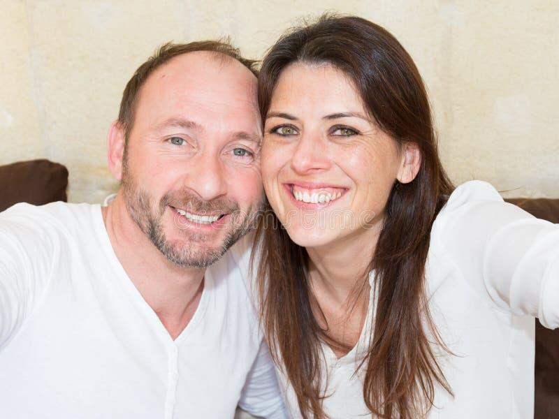 做selfie和微笑的愉快的片刻一起愉快的年轻爱恋的夫妇 免版税库存照片