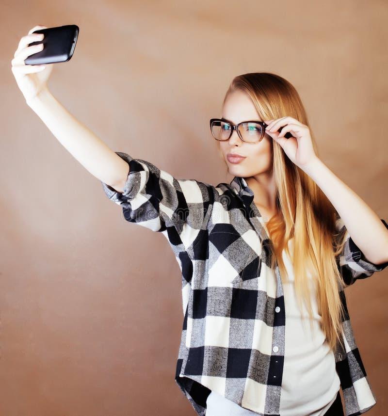 做selfie在学校,s的玻璃的年轻俏丽的女孩少年 库存照片