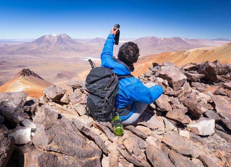 做selfie山峰,背面图,玻利维亚的旅游背包徒步旅行者 免版税库存照片
