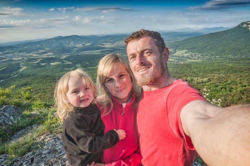做selfie山谷背景的家庭远足者 免版税库存照片