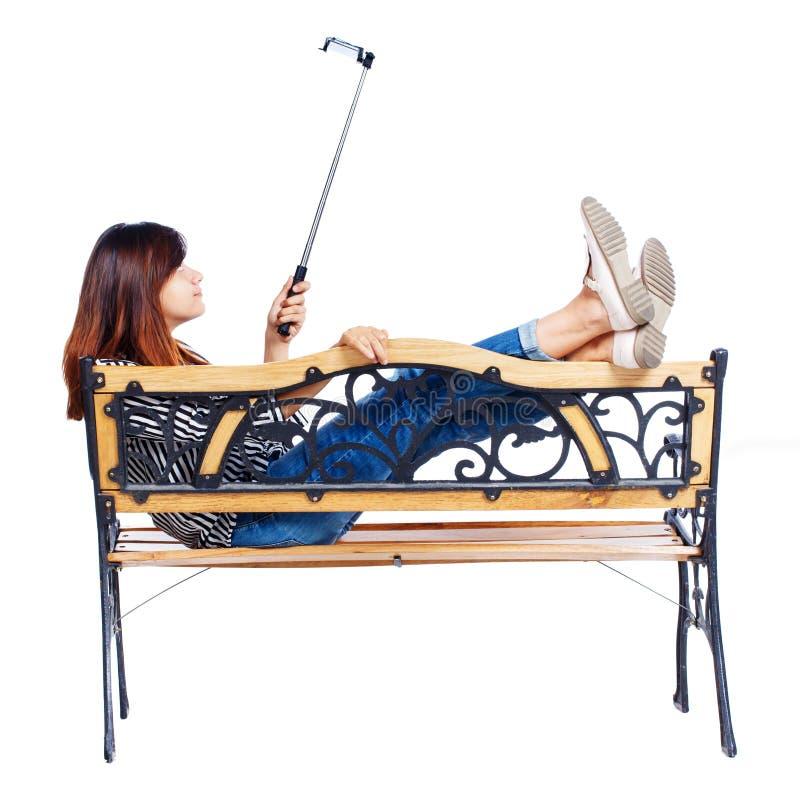做selfie棍子画象的后面观点的妇女坐长凳 库存照片