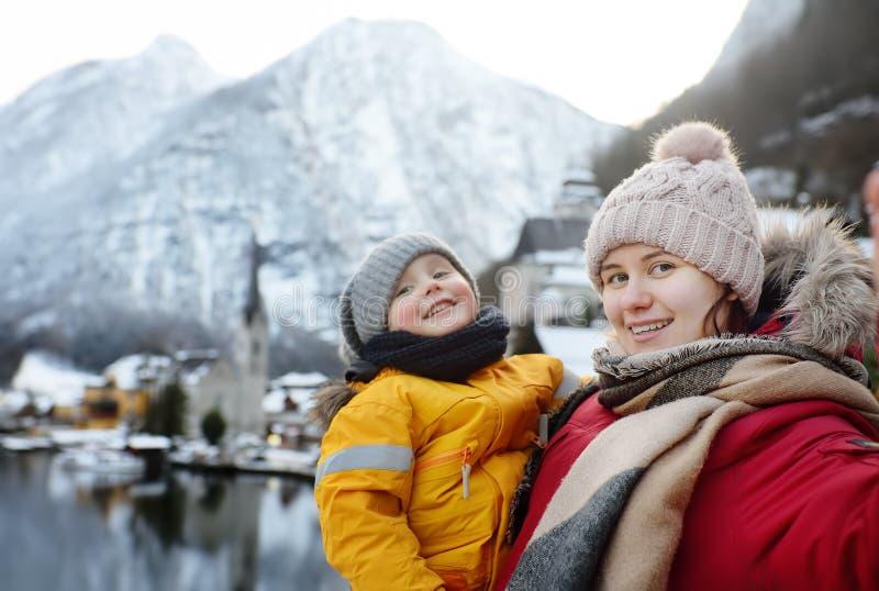 做selfie流动照片有Hallstatt村庄冬天风景视图的少妇和她的小儿子在背景 免版税库存图片
