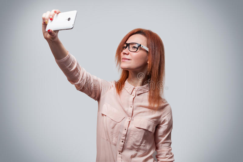做selfie照片的一名年轻可爱的妇女的画象在智能手机隔绝了灰色背景 免版税库存图片