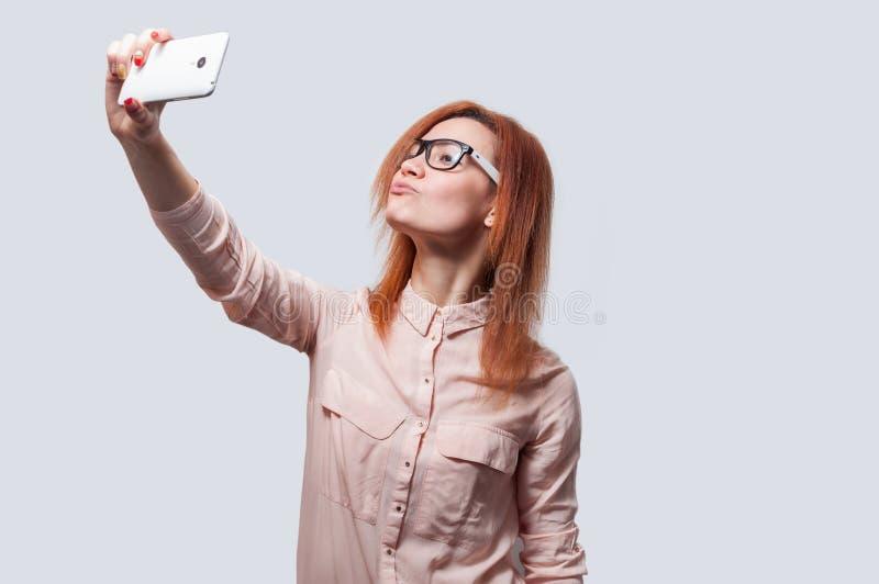 做selfie照片的一名年轻可爱的妇女的画象在灰色背景隔绝的智能手机 免版税库存图片