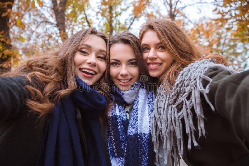 做selfie照片的三个女朋友在照相机 图库摄影