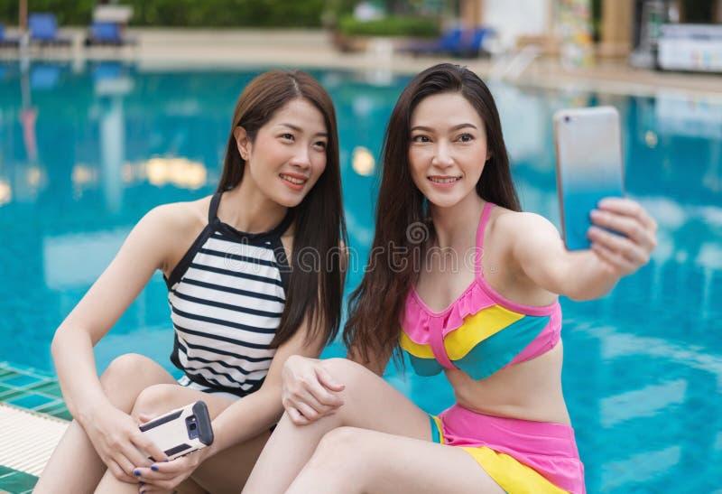 做selfie照片的泳装的妇女在游泳的智能手机 免版税库存照片