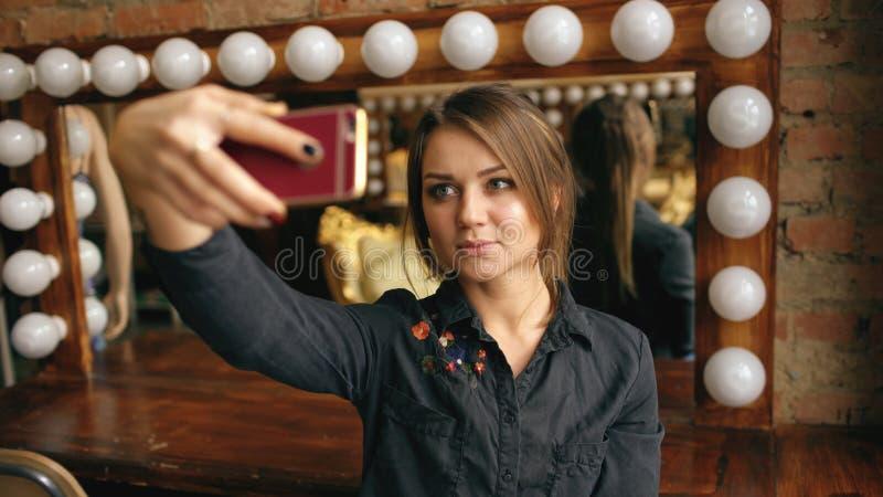做selfie画象的美丽的少妇在一个智能手机在化装室户内 免版税库存图片