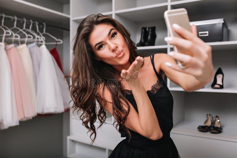 做selfie的一个美丽的深色的女孩的Selfie画象使用一智能手机,在她的化装室 她送一个亲吻 免版税图库摄影